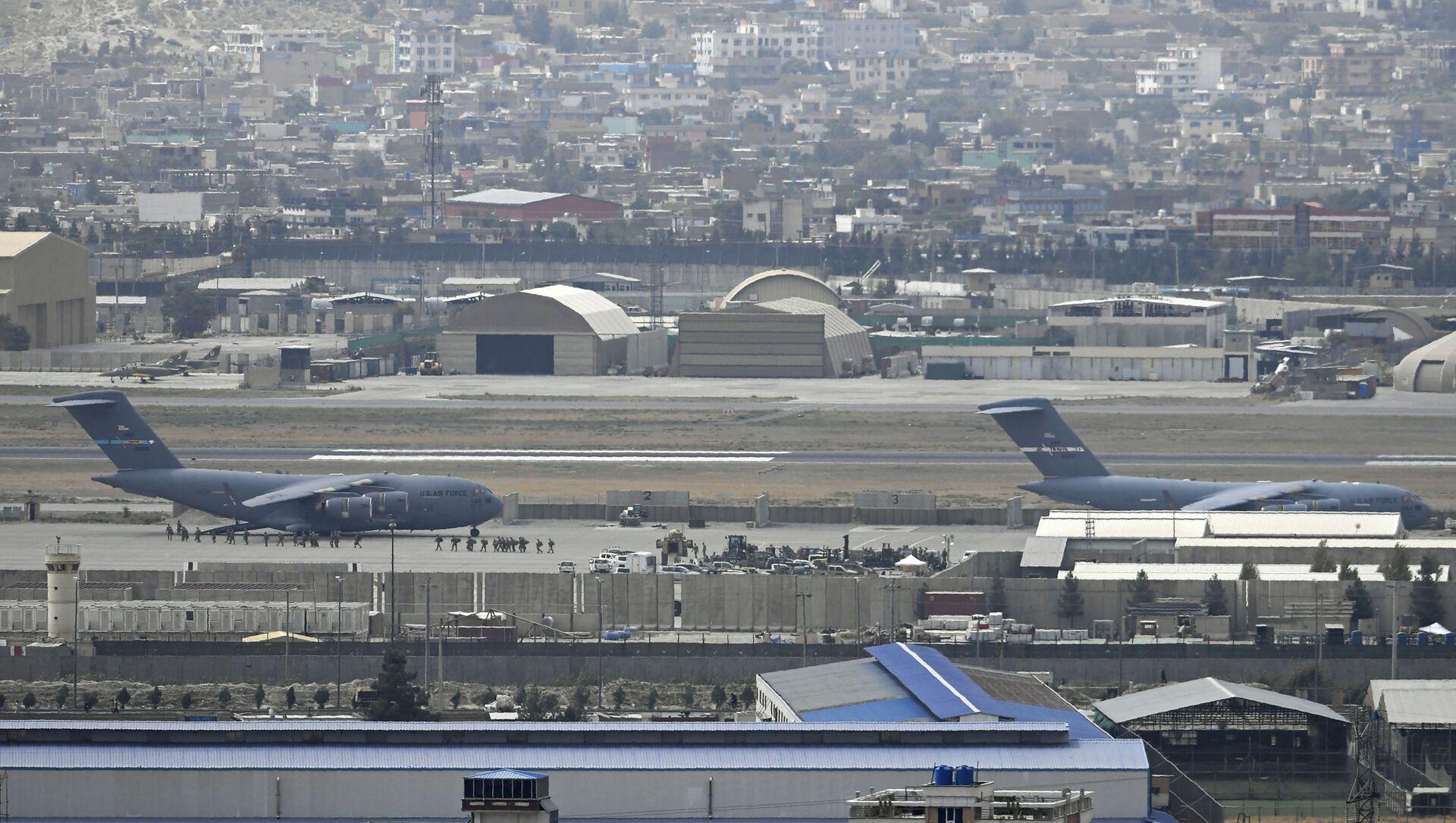 Солдаты США садятся в самолет ВВС США в аэропорту Кабула 30 августа 2021 года. - 30 августа были выпущены ракеты по аэропорту Кабула, где американские войска спешили завершить свой вывод из Афганистана и эвакуировать союзников под угрозой со стороны группировки «Исламское государство». атаки. - Sputnik Аҧсны, 1920, 31.08.2021