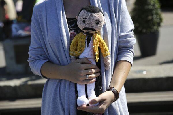 Поклонник держит куклу  Фредди Меркьюри рядом с его памятником в Монтре. - Sputnik Абхазия