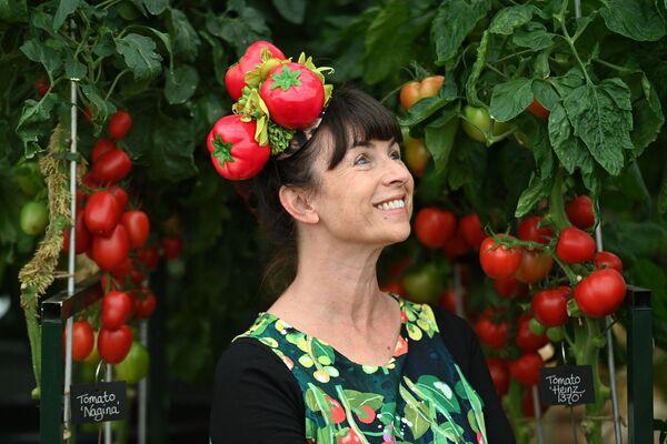 Женщина в шляпе с томатами во время цветочной выставки RHS Chelsea в Лондоне. - Sputnik Абхазия