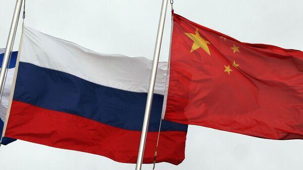 Государственные флаги России (слева) и Китая во время церемонии открытия Армейских международных игр-2021 (АрМИ-2021) во Владивостоке. - Sputnik Абхазия