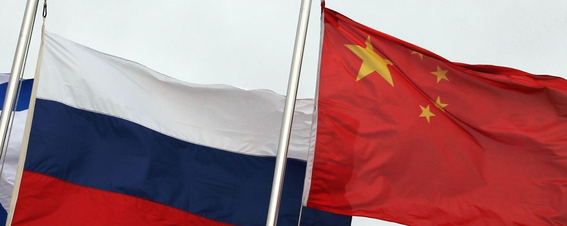 Государственные флаги России (слева) и Китая во время церемонии открытия Армейских международных игр-2021 (АрМИ-2021) во Владивостоке. - Sputnik Абхазия, 1920, 28.03.2021