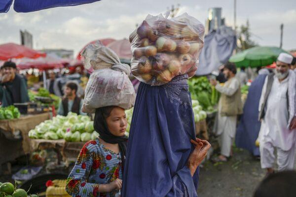 Женщина в парандже несет на голове мешок с луком на рынке в Кабуле. - Sputnik Абхазия