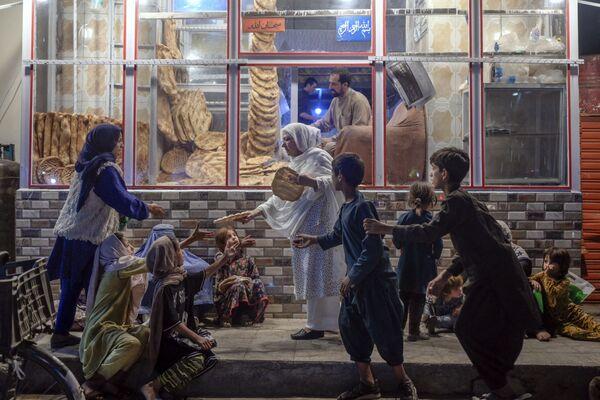 А эта женщина раздает хлеб нуждающимся детям перед пекарней в Кабуле. - Sputnik Абхазия