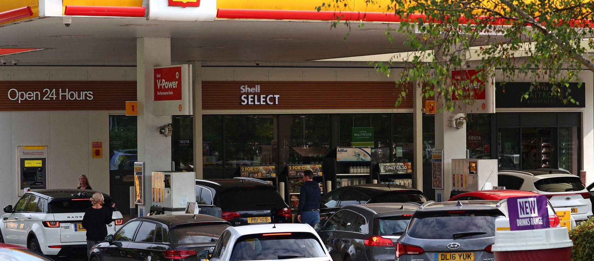Автомобилисты выстраиваются в очередь, чтобы заправить свои автомобили бензином или дизельным топливом у бензозаправочного центра Shell возле Фарнборо, к западу от Лондона - Sputnik Абхазия, 1920, 27.09.2021