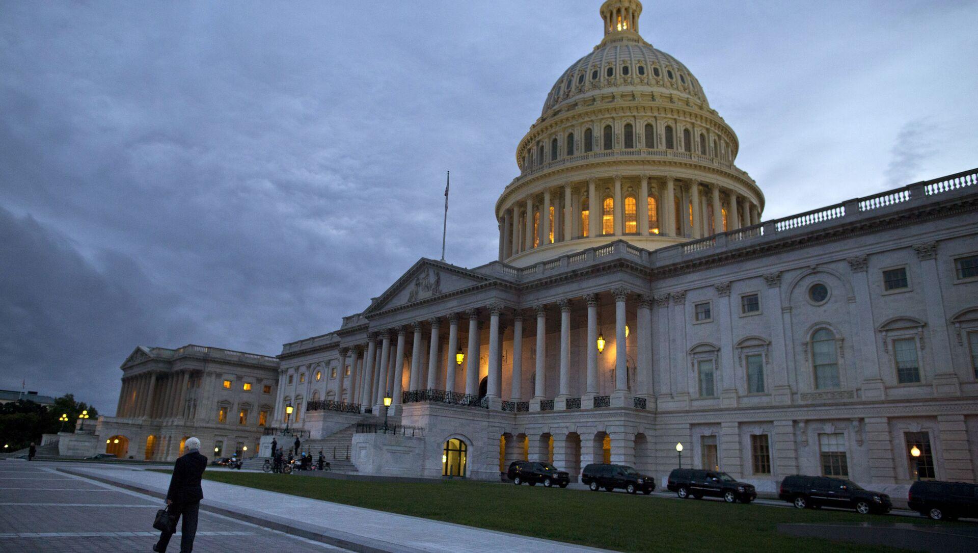 На этой фотографии от 15 октября 2013 года показан вид на здание Капитолия США в сумерках в Вашингтоне. Даже если Конгресс достигнет в последнюю минуту или нарушит крайний срок сделку, чтобы предотвратить федеральный дефолт и полностью открыть правительство, выборные должностные лица, вероятно, вернутся к своей жесткой марке балансирования на грани войны, возможно, неоднократно. Переговоры между Палатой представителей и Сенатом почти не затрагивают глубинные причины тупика с долгами и расходами, который подтолкнул страну к экономическому кризису в 2011 году, в декабре прошлого года и снова в этом месяце. - Sputnik Абхазия, 1920, 28.09.2021