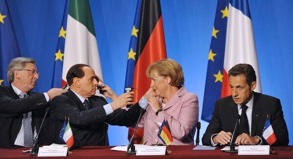 Жан-Клод Юнкер и Сильвио Берлускони помогают Ангеле Меркель использовать наушники во время пресс-конференции с Николя Саркози, Франция. - Sputnik Абхазия