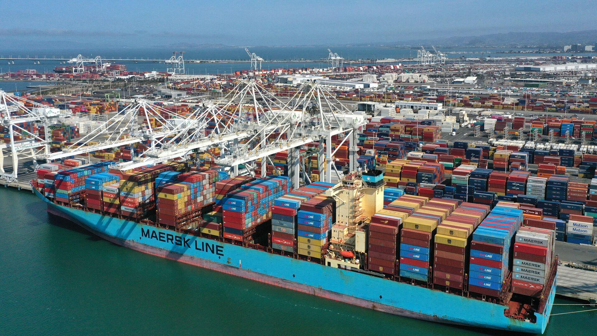 ОКЛЕНД, КАЛИФОРНИЯ - 9 СЕНТЯБРЯ: С высоты птичьего полета морские контейнеры сидят на контейнеровозе в порту Окленда 9 сентября 2021 года в Окленде, Калифорния. Поскольку пандемия COVID-19 продолжается, нехватка транспортных контейнеров привела к резкому росту цен на контейнеры и нарушила цепочку поставок. Год назад стоимость аренды контейнера составляла около 1900 долларов, сейчас - около 14000 долларов. Стоимость стандартного 40-футового контейнера увеличилась вдвое. Джастин Салливан - Sputnik Абхазия, 1920, 06.10.2021
