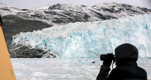 Турист смотрит на ледник Экип Сермия в Гренландии - Sputnik Абхазия
