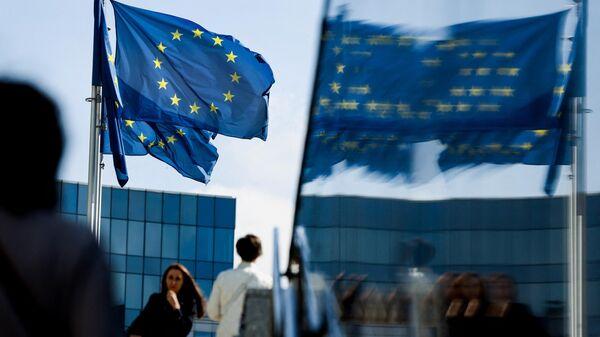 Люди идут перед флагом Евросоюза в районе штаб-квартиры ЕС в Брюсселе 23 сентября 2021 г. - Sputnik Абхазия