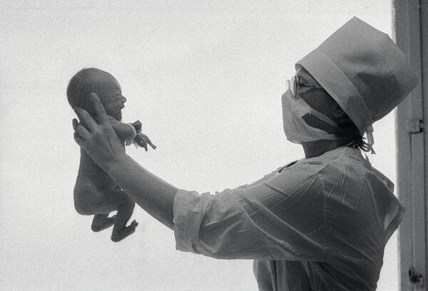 Акушер держит новорожденного. Архивное фото - Sputnik Абхазия