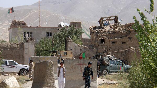 Афганский полицейский на фоне здания тюрьмы после нападения в провинции Газни, Афганистан 14 сентября 2015. - Sputnik Аҧсны