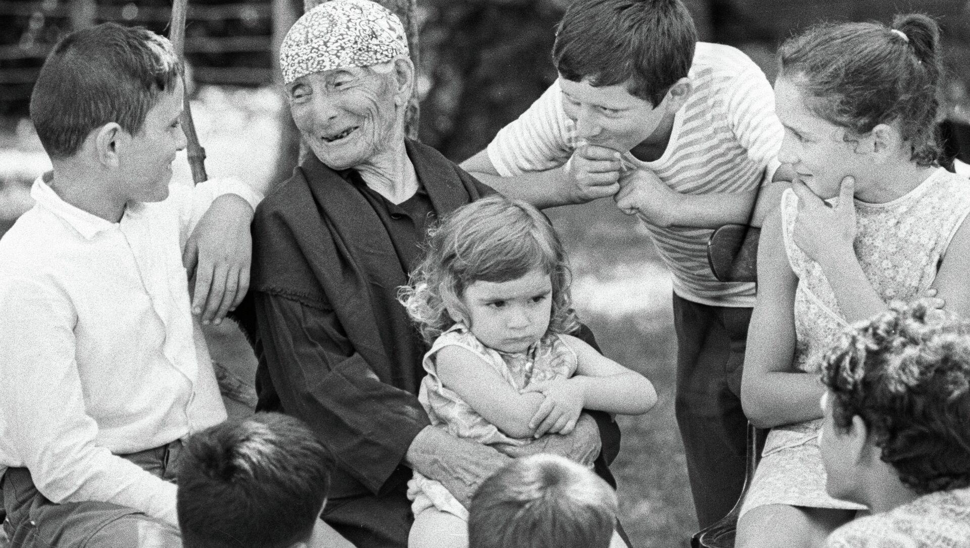 Женщина-долгожитель Хьфаф Ласурия (137 лет) из села Кутол в окружении правнуков. - Sputnik Аҧсны, 1920, 27.02.2021