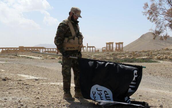 Член сирийских проправительственных сил несет флаг группы Исламского государства (IS), в древнем городе Пальмира 27 марта 2016 года. - Sputnik Абхазия