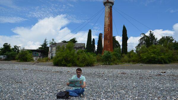 Корреспондент Sputnik Владимир Бегунов на фоне сухумского маяка - Sputnik Абхазия
