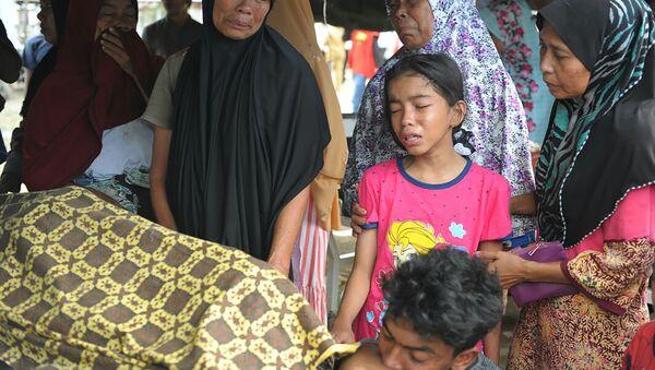 Семья оплакивает своего родственника, который умер после мощного землетрясения в Индонезии - Sputnik Абхазия