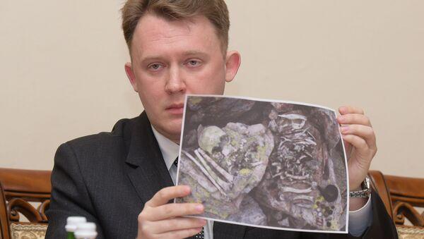 Историк Николай Медвенский показывает фотографию останков советских солдат - Sputnik Абхазия
