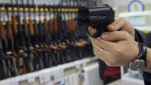 Покупатель осматривает травматический пистолет Оса в одном из оружейных магазинов Москвы - Sputnik Абхазия
