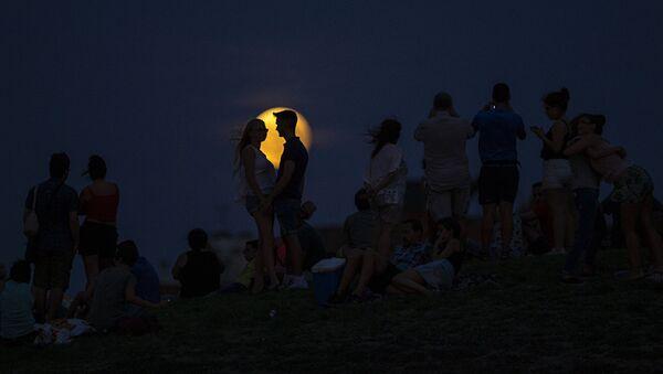 Люди наблюдают за восхождением полной луны во время ее частичного затмения на вершине холма в парке в Мадриде. - Sputnik Абхазия