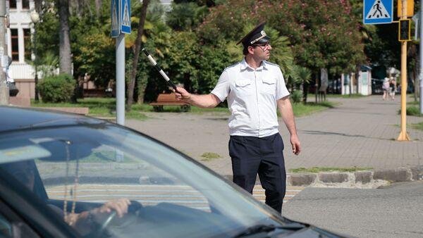 Работник ГАИ регулирует движение на перекрестке со сломанным светофором - Sputnik Абхазия