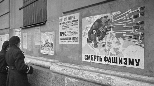 Девушки читают листовки на стене дома - Sputnik Абхазия
