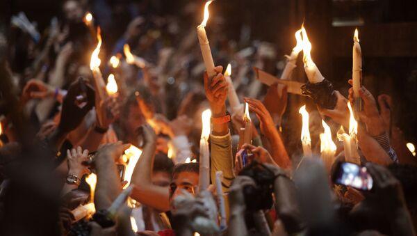 Верующие со свечами во время сошествия благодатного огня в Храм Гроба Господня в Иерусалиме - Sputnik Абхазия