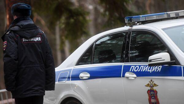 Сотрудник полиции возле служебного автомобиля - Sputnik Абхазия
