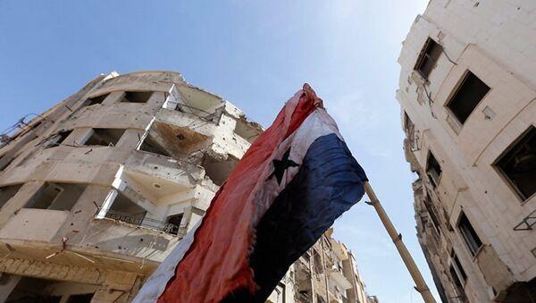 Сирийский флаг на разрушенной улице в Восточной Гуте - Sputnik Абхазия