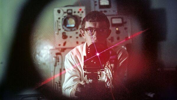 Инженер института Олег Сакаев работает с квантовым генератором - Sputnik Абхазия