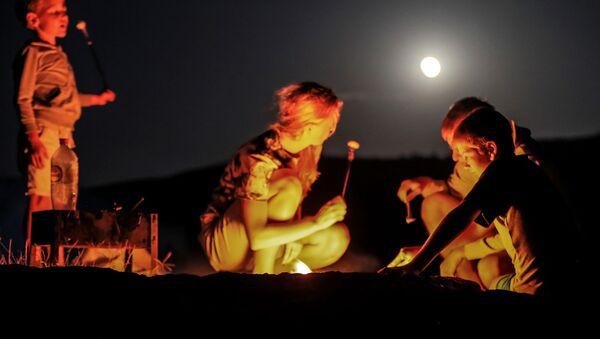 Туристы во время полного лунного затмения над мысом Меганом в Крыму - Sputnik Абхазия