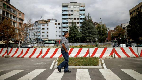Мужчина проходит мимо бетонного барьера в конце главного моста через реку Ибар в Митровице, Косово, 5 сентября 2018 года - Sputnik Абхазия
