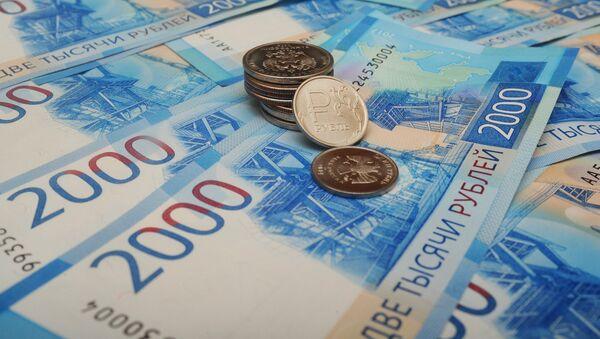 Банкноты номиналом 2000 рублей и монета 1 рубль с графическим обозначением символа рубля. - Sputnik Аҧсны