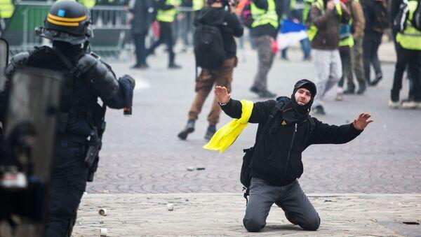 Сотрудник правоохранительных органов и активист во время протестной акции движения автомобилистов желтые жилеты, выступавшего с требованием снижения налогов на топливо, в районе Триумфальной арки в Париже - Sputnik Абхазия