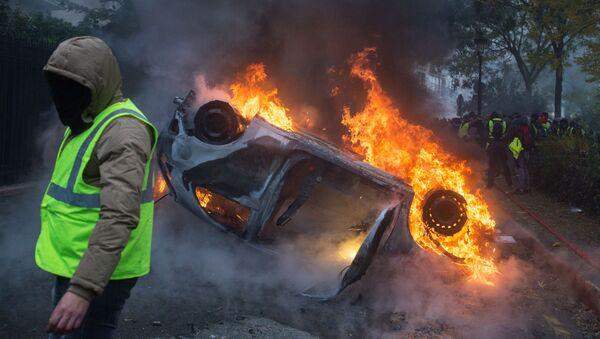 Автомобиль, горящий во время протестной акции движения автомобилистов желтые жилеты, выступавшего с требованием снижения налогов на топливо в Париже - Sputnik Аҧсны