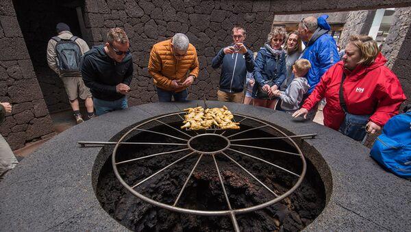 Туристы в ресторане El Diabolo, в котором еду готовят над кратером вулкана, Лансароте, Испания - Sputnik Абхазия