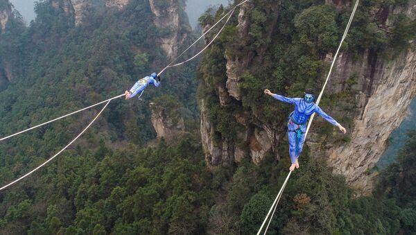 Два участника, одетые как персонажи из фильма «Аватар», во время соревнования по слэклайну в горах Хуаншичжай в центральной китайской провинции Хунань - Sputnik Абхазия