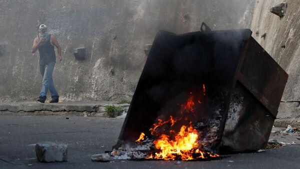 Демонстрант за горящей баррикадой во время протестов в Каракасе, Венесуэла - Sputnik Абхазия