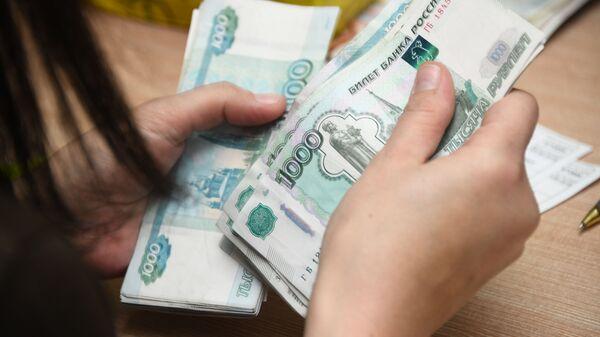 Работник почтамта пересчитывает деньги. - Sputnik Аҧсны
