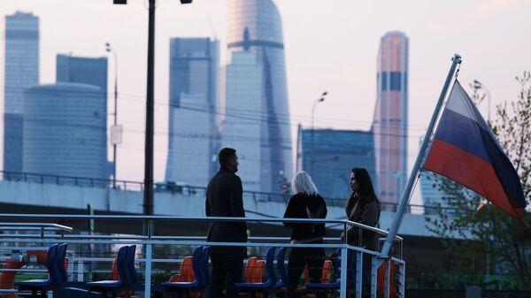 Люди на палубе теплохода во время прогулки по Москве-реке. На втором плане: небоскребы делового центра Москва-сити - Sputnik Абхазия