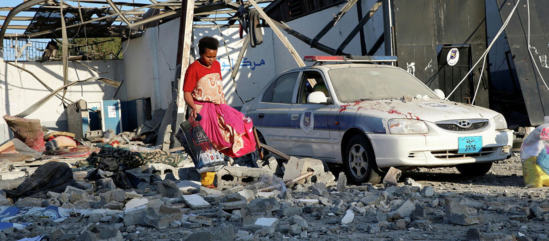 Мигрант собирает целую одежду после авианалета на лагерь беженцев в Ливии. 3 июля 2019  - Sputnik Абхазия, 1920, 22.01.2020