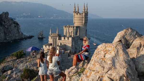 Отдыхающие фотографируются возле замка Ласточкино гнездо на береговой скале в поселке Гаспра в Крыму - Sputnik Абхазия