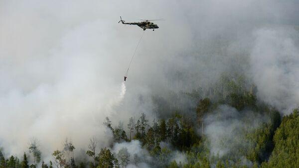 Вертолет Ми-8 с водосливной системой для забора воды в открытых водоемах во время тушения лесных пожаров в Красноярском крае - Sputnik Абхазия