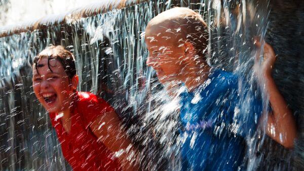 Горожане спасаются от жары у фонтана - Sputnik Абхазия