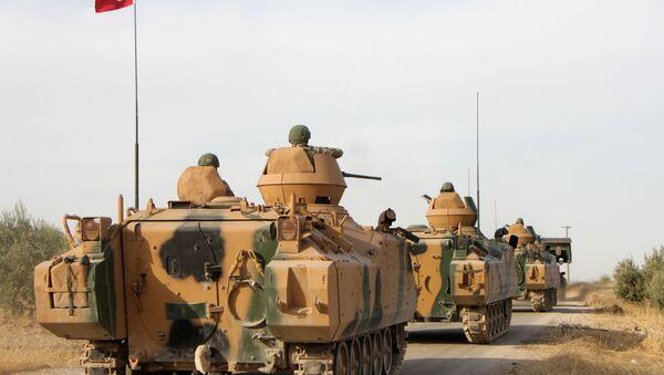 Турецкие солдаты перевозятся на бронетранспортерах через город Тухар, к северу от северного сирийского города Манбидж, 14 октября 2019 года, когда Турция и ее союзники продолжают наступление на удерживаемые курдами пограничные города на северо-востоке Сирии. - Sputnik Абхазия