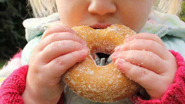 Ребенок ест пончик. Архивное фото - Sputnik Абхазия