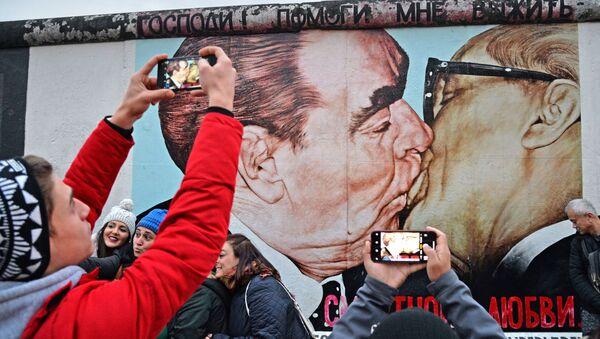 Люди у фрагмента Берлинской стены (East-Side Gallery) на Мюленштрассе с произведением Дмитрия Врубеля Господи! Помоги мне выжить среди этой смертной любви или Братский поцелуй (поцелуй Брежнева и Хонеккера) - Sputnik Абхазия