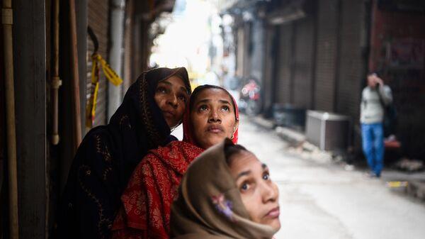 Женщины смотрят на пожар на фабрике в Нью-Дели, Индия - Sputnik Абхазия