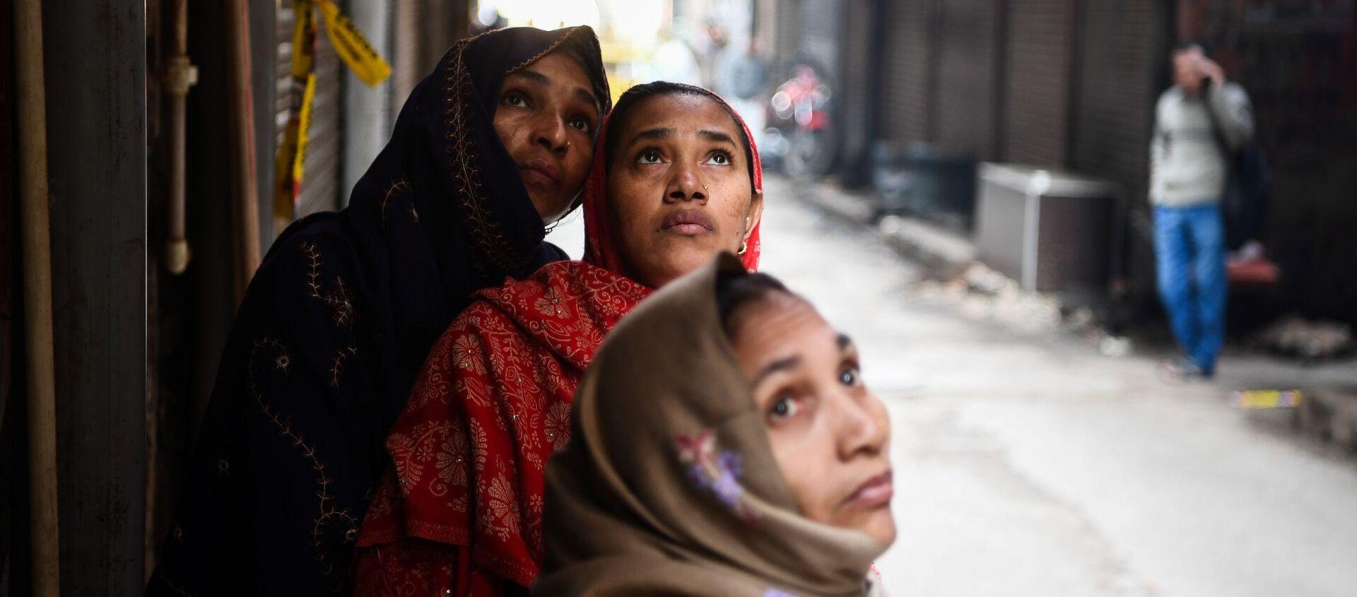 Женщины смотрят на пожар на фабрике в Нью-Дели, Индия - Sputnik Абхазия, 1920, 25.09.2021