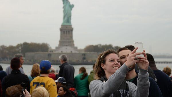 Туристы фотографируются на фоне Статуи Свободы в Нью-Йорке. - Sputnik Абхазия