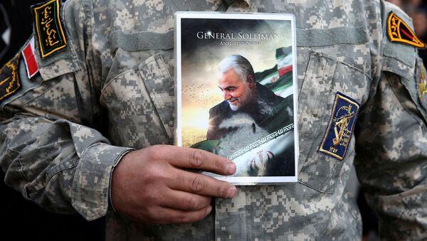 Мужчина держит портрет убитого генерала Сулеймани - Sputnik Абхазия