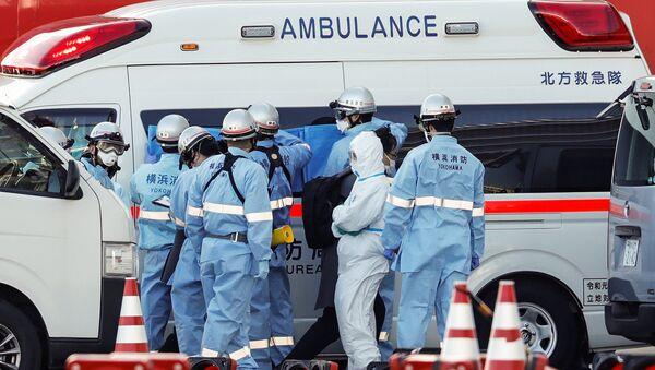 Пожарные в защитных костюмах помещают в машину скорой помощи заболевших пассажиров круизного лайнера Diamond Princes, помещенного в карантин у японского порта Йокогама - Sputnik Абхазия